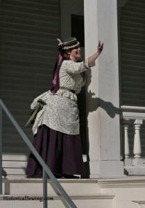 Waving to friends in 1871 bustle dress